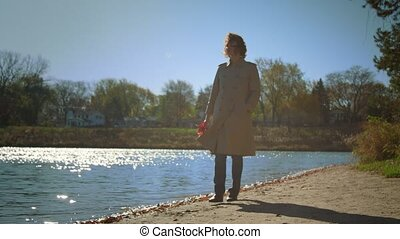 Beautiful woman in autumn clothes walking along the sandy shore of the lake