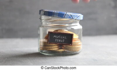 MUTUAL FUNDS idea - text and coins - writing MUTUAL FUNDS...