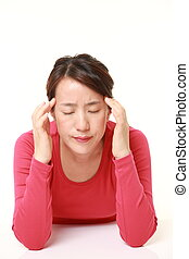 woman suffers from headache - studio shot of middle aged...