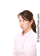 middle aged Japanese woman in a bad mood - studio shot of...