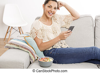 Happy woman texting - Beautiful woman sitting on a sofa with...