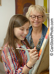 young teen girl painting with her teacher