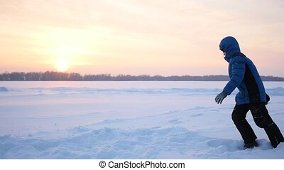 teen plays on the Playground in winter. flips in the snow at...