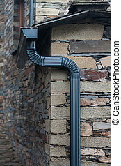 Plastic water pipe on a schist house.