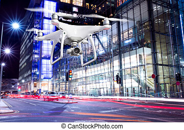 Hovering drone taking pictures of city of London at night -...