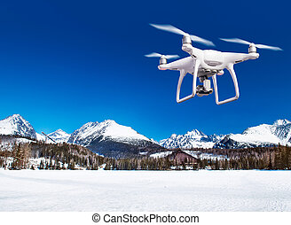 Hovering drone taking pictures of white winter nature -...