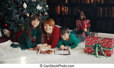 Family Book Reading near Christmas Tree - Mother with her...