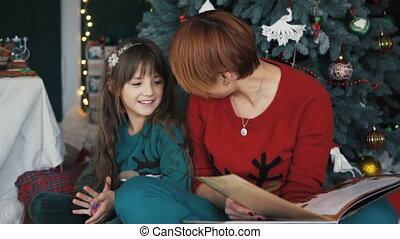 Mother with Daughter near Christmas Tree