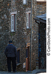 old man walking down the street on a schist town.