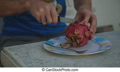 Cutting a Pitahaya Dragon Fruit closeup shot hand - Cutting...