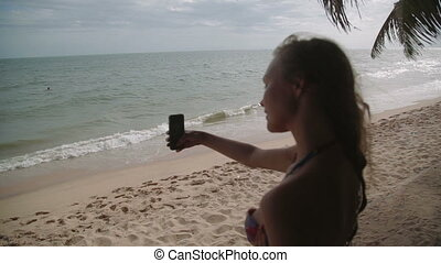 Beach vacation people - woman white bathing suit makes selfie relaxing looking at perfect paradise asian sea . Girl in bikini sunbathing on travel holidays SLOW MOTION shot