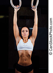Crossfit. Portrait of young fit muscular girl in white top...