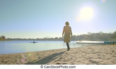 Woman goes on the sandy shore to the lake.