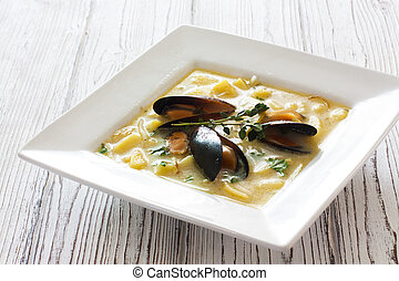 Soup with mussels and potatoes in white plate over white...