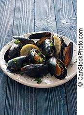 Mussels on white plate over blue wood background - Mussels...