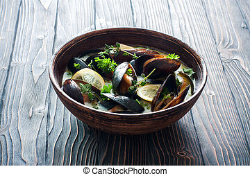 Mussels in clay pot over dark wood background - Mussels...