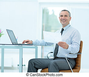 successful smiling businessman with documents is sitting on the