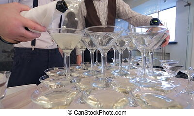 Two sommeliers pour champagne in goblets close up, wedding...
