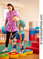 cute kid having physical musculoskeletal therapy in...