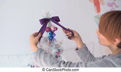 Happy Woman Dressing up the Christmas Tree - Woman in grey...