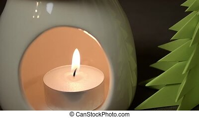 Burning candle in aroma lamp with origami tree, holiday...