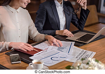 Two female colleagues doing work together in office - Great...