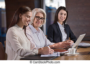 Pretty young female colleagues and their boss working in...