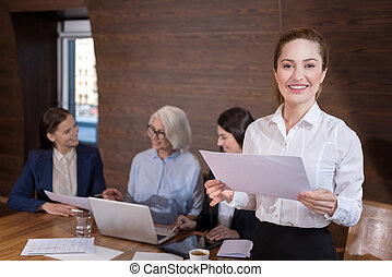Delighted woman posing in office with documents and...