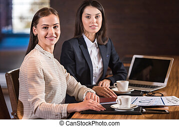 Beautiful female colleagues posing together in office - Best...