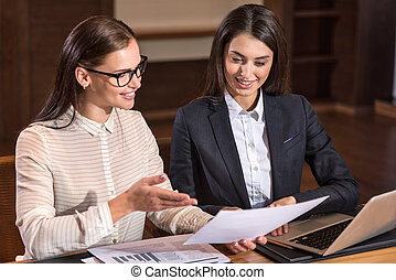 Joyful female colleagues discussing project in office -...