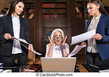 Exhausted boss and her female colleagues posing in an office...