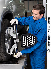 Professional mechanic adjusting automobile wheel system