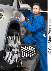 Pleasant mechanic adjusting automobile wheel alignment