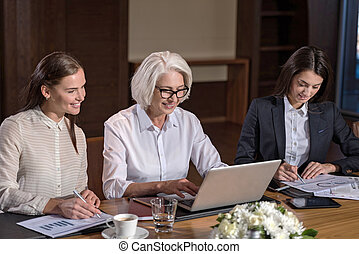 Two young female colleagues and their boss working together...