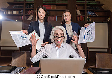 Tired boss and her female colleagues posing in office -...