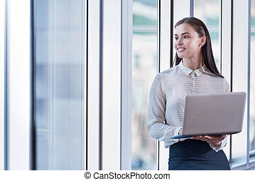 Brunette woman using laptop in an office - Always in touch....