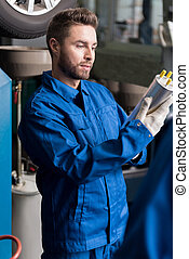 Concentrated mechanic examining oil filter - Everything is...