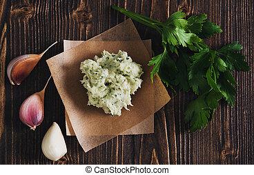 Lard with salt, garlic and herbs, wooden background