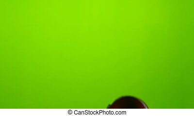 Player's hand raises a red protective helmet. Green screen -...