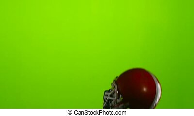 American football picks up a red protective helmet. Green...
