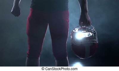 Football player holding a red protective helmet. Black...