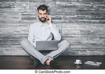Man on phone using laptop