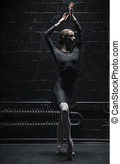 Slim female dancer training near the wall - Ballet dancer....