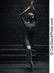 Slim female dancer training near the wall - Ballet dancer....