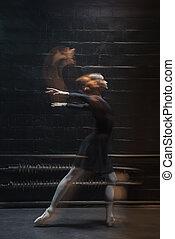 Graceful dancer warming up on the dark background - Graceful...