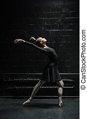 Flexible female dancer stretching in the black room -...