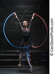 Charismatic ballet dancer dancing with a colorful gymnastic...