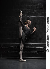 Young dancer training near the black wall - Full of...