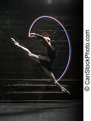 Graceful ballet dancer jumping with a colorful gymnastic...