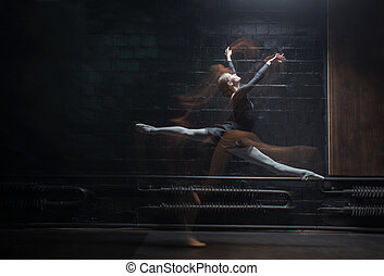Young female gymnast showing her twine on the dark...